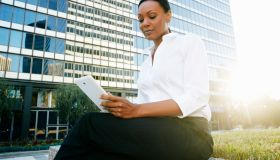 Black businesswoman using digital tablet outdoors
