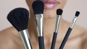 Woman holding four make-up brushes