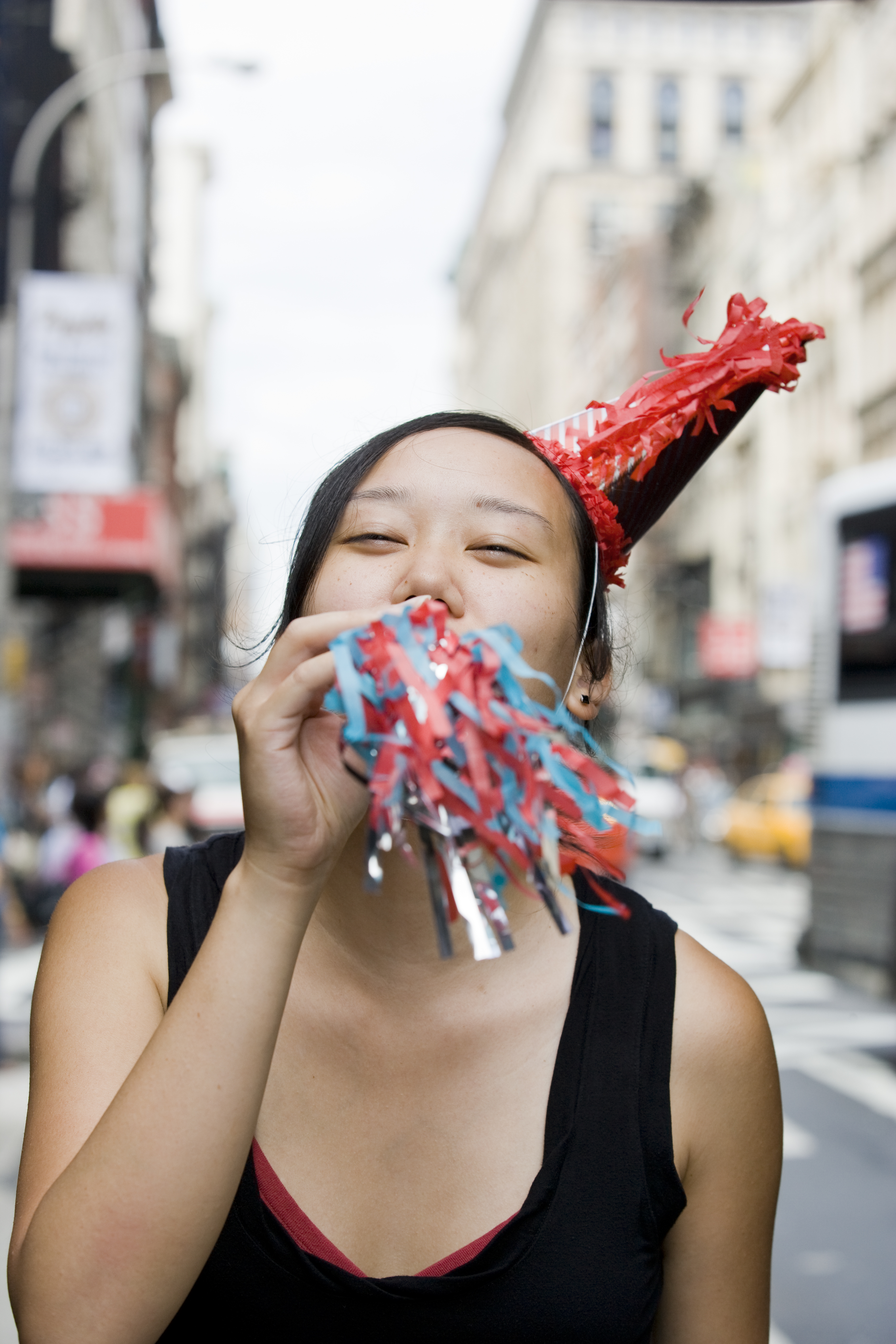 Young Korean woman blowing party horn in downtown city