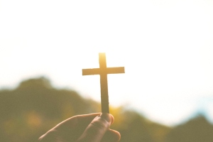 Close-Up Of Hand Holding Cross Against Sky